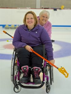 two wheelchair curlers smiling